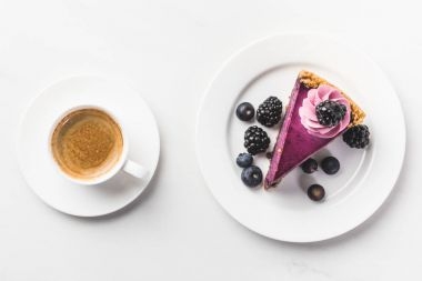 top view of piece of cake with berries and cup of coffee isolated on white tabletop