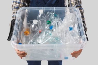 partial view of man holding container with plastic bottles in hands isolated on grey, recycling concept