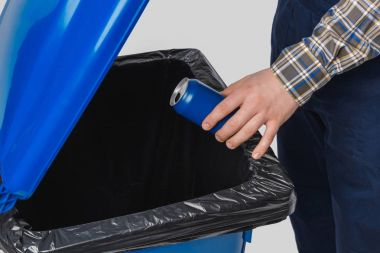 partial view of cleaner putting can into trash bin isolated on grey