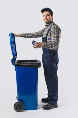 side view of young cleaner in uniform with can standing at trash bin isolated on grey