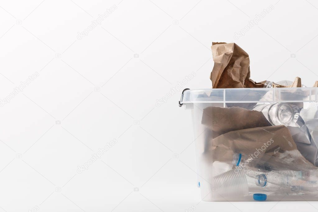 close up view of container with paper and plastic garbage isolated on white, recycling concept