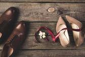 flache Lage mit Schleife, Corsage, Braut- und Bräutigamsschuhen auf hölzerner Tischplatte