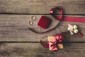 Fotografie flache Lay mit Schleife, Trauringe, Corsage und Geschenk auf hölzernen Tischplatte