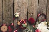 Fotografie flache Lay mit Trauringe, Schmuck-Box, Brautstrauß und die Corsage auf hölzernen Tischplatte
