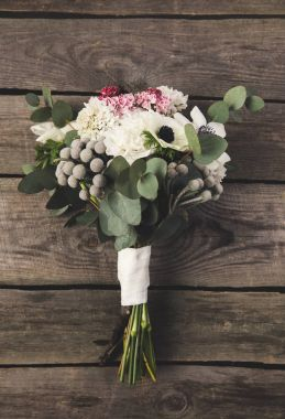 top view of beautiful bridal bouquet on wooden surface