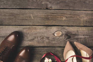 flat lay with ribbon, corsage, bridal and grooms shoes on wooden tabletop