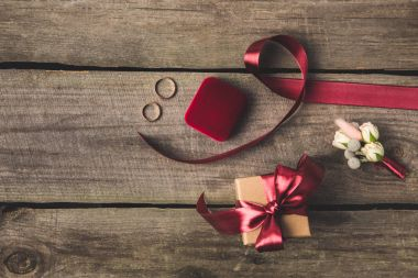 flat lay with ribbon, wedding rings, corsage and gift on wooden tabletop