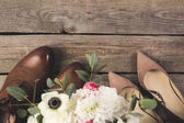 Draufsicht von Braut- und Bräutigamsschuhen mit Blumenstrauß auf Holztischplatte