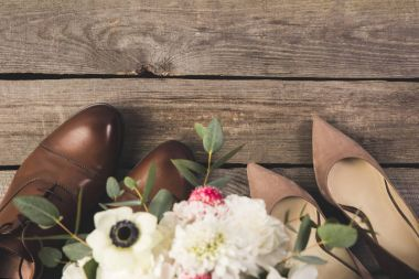top view of pairs of bridal and grooms shoes with bouquet of flowers on wooden tabletop