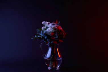 bouquet of white flowers in glass vase on dark