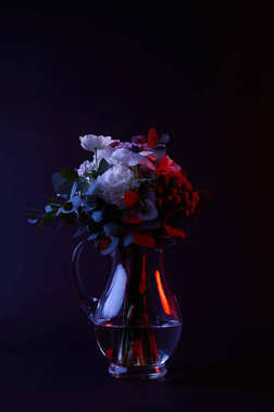 bouquet of different flowers in reflecting glass vase on dark