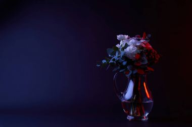 bouquet of different flowers in carafe with water on dark