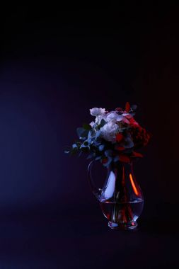 bouquet of different flowers in glass carafe with water on dark