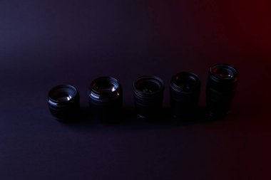 high angle view of row of camera lenses on dark surface