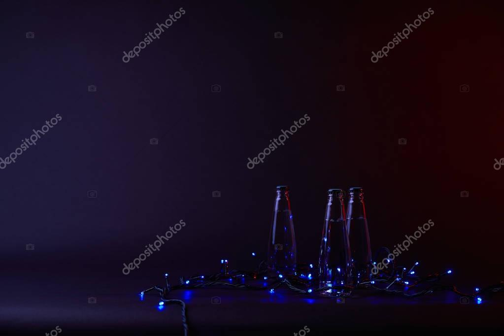 three bottles of water with blue shining garland on dark surface