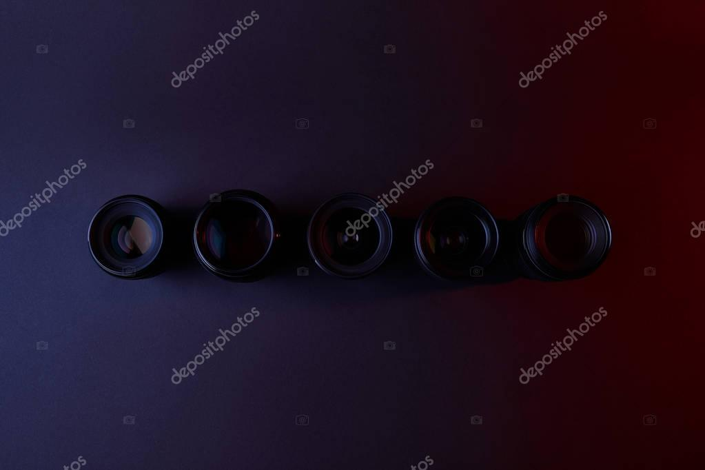 top view of row of camera lenses on dark