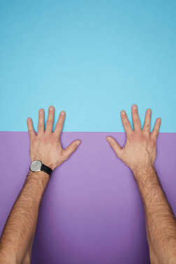 cropped shot of male hands on blue and violet colored paper