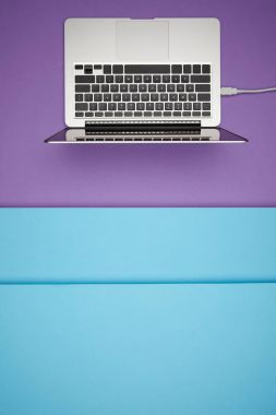 Top view of laptop on purple and blue paper background stock vector