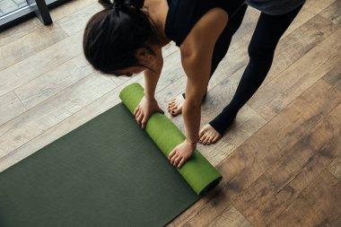 high angle view of girl putting yoga mat on floor