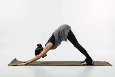 woman practicing yoga and doing downward facing dog isolated on white