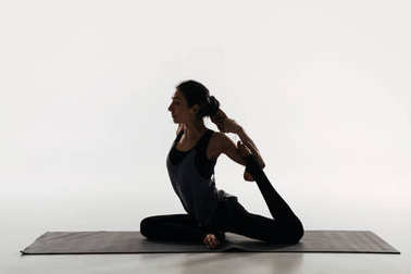 side view of woman practicing yoga and doing king pigeon on white
