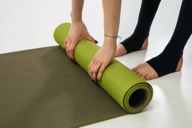 cropped image of woman putting yoga mat on floor