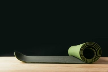 green rolled yoga mat on wooden table on black