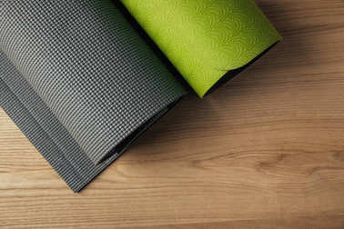 top view of two green and grey yoga mats on wooden floor