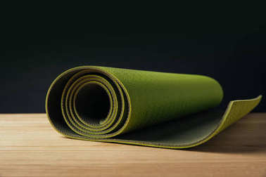 green rolled yoga mat on wooden surface on black