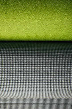 top view of two green and grey rolled yoga mats