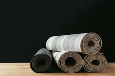 different rolled yoga mats on wooden table