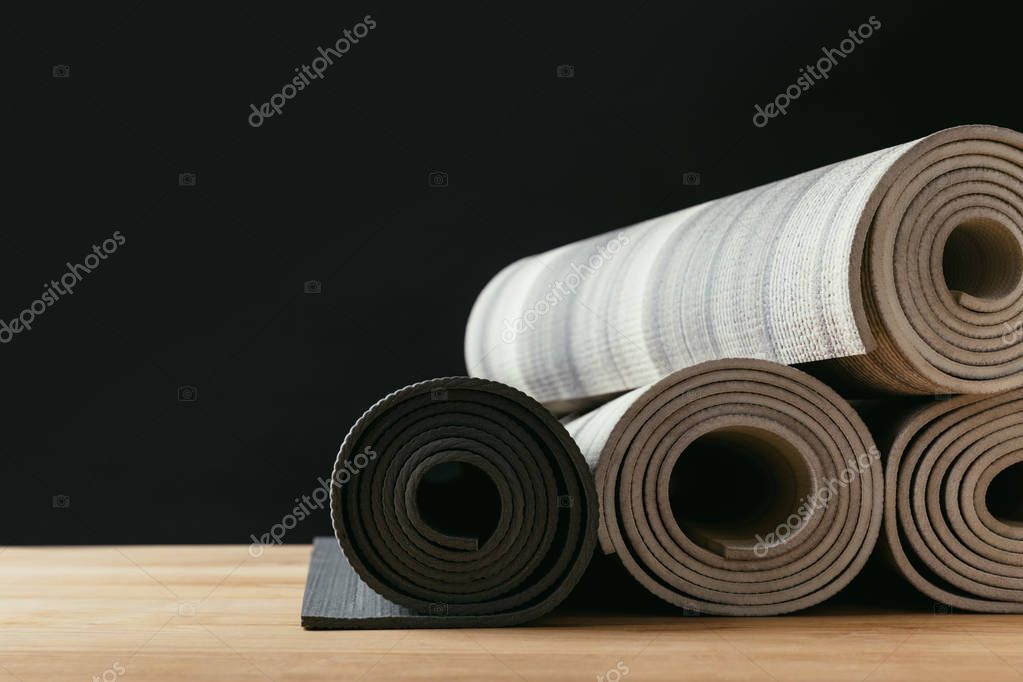 different rolled yoga mats on wooden tabletop