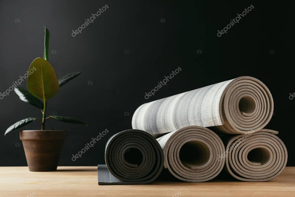 different rolled yoga mats and potted plant on wooden table