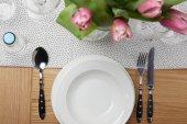 Fotografia Stoviglie da tavola con i piatti sul tavolo con fiori in vaso