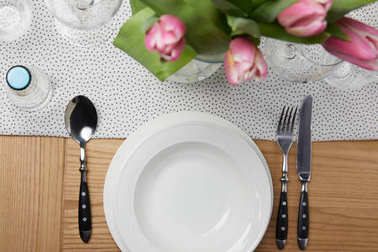 Dinnerware with plates on table with flowers in vase