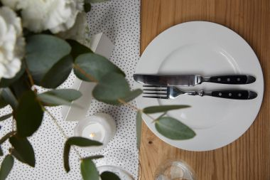 Table setting with cutlery on plate on table with flowers