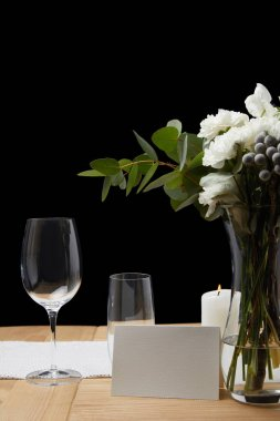 Tender flowers in vase with glasses on table next to blank card on black background