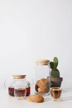 tea in glass cups, tasty cookies, teapot and cactus in pot on grey