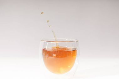 close-up view of pouring fresh hot tea in glass cup on grey