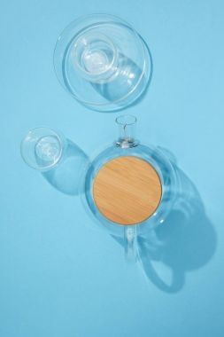 top view of empty glass teapot with cup, plate and bowl on blue