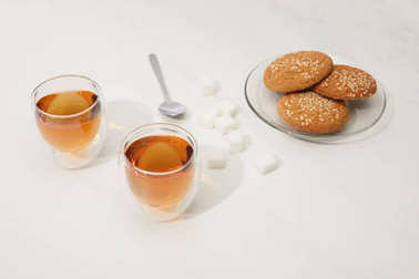 Close-up view of tea in glass cups, spoon, sugar cubes and oatmeal cookies on plate on grey stock vector