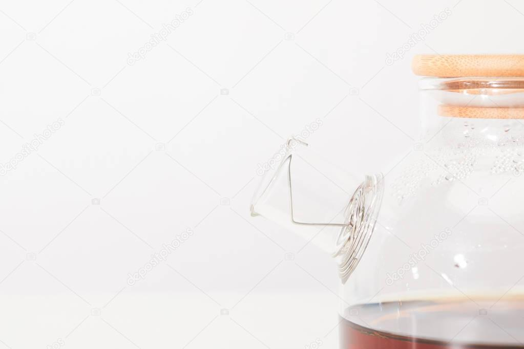 close-up view of glass kettle with fresh herbal tea on grey