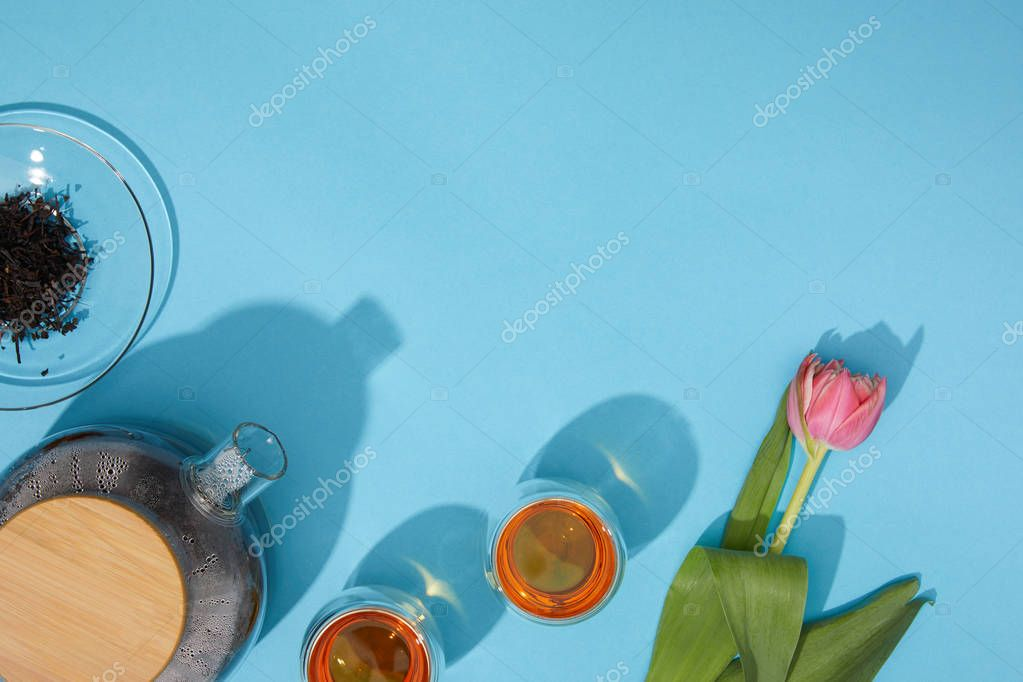 top view of fresh hot tea in cups and teapot and beautiful tulip flower on blue
