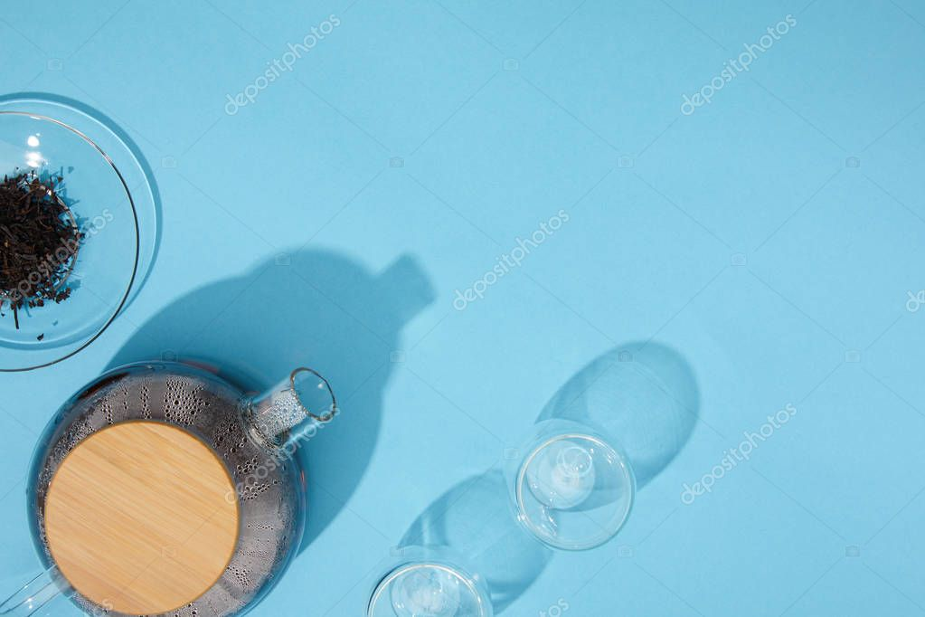 top view of kettle with fresh tea, empty glasses and dry herbal tea in bowl on blue