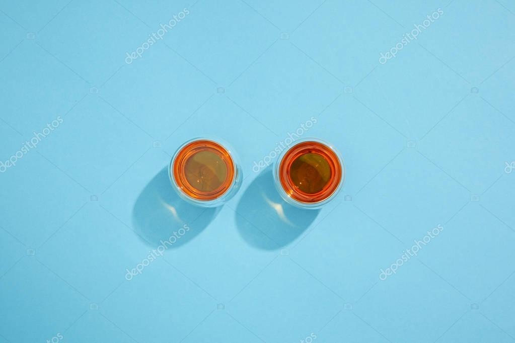 top view of cups with fresh hot tea and shadows on blue
