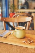 Photo Cocoa drink with orange peel and nuts on table