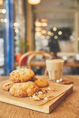 Homemade chocolate chip cookies on wooden table with flat white coffee