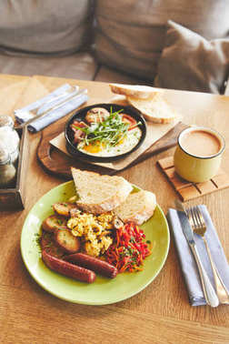 Hot breakfast dish of fried eggs and coffee on table