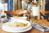 Fotografie Heiße italienischer Pasta mit Pilzen und Pesto serviert mit Wein