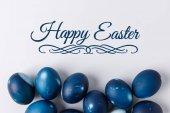 Fotografie Draufsicht der blau bemalte Ostereier mit glücklich Ostern Schriftzug auf weißem